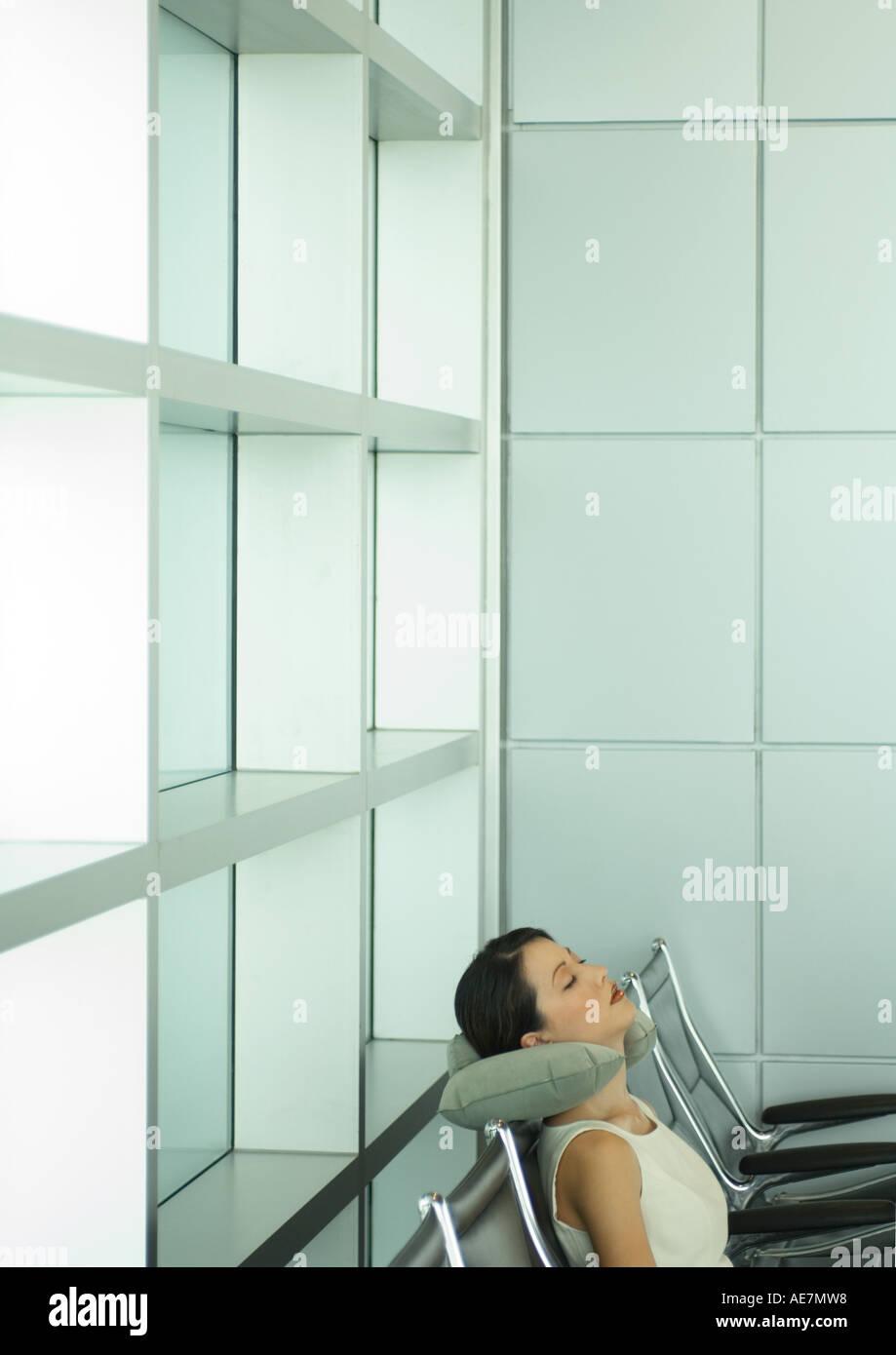 Frau schläft in Flughafen-Lounge, mit Nackenkissen Stockbild