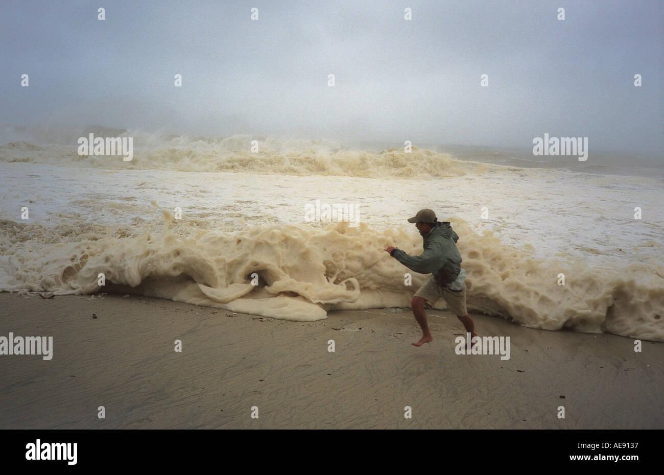 Mann läuft vor Annäherung an Welle, verursacht durch den Hurrikan Ignacio Baja California Mexiko Modell veröffentlicht Bild Stockbild