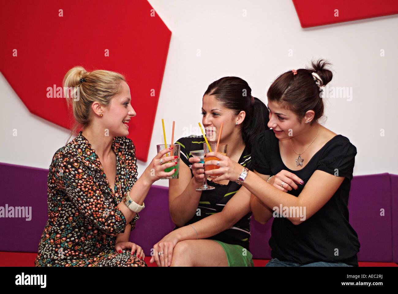 Drei junge Frauen in einer Bar in einer Nacht erhöhen ihre Gläser in einem Toast Stockfoto