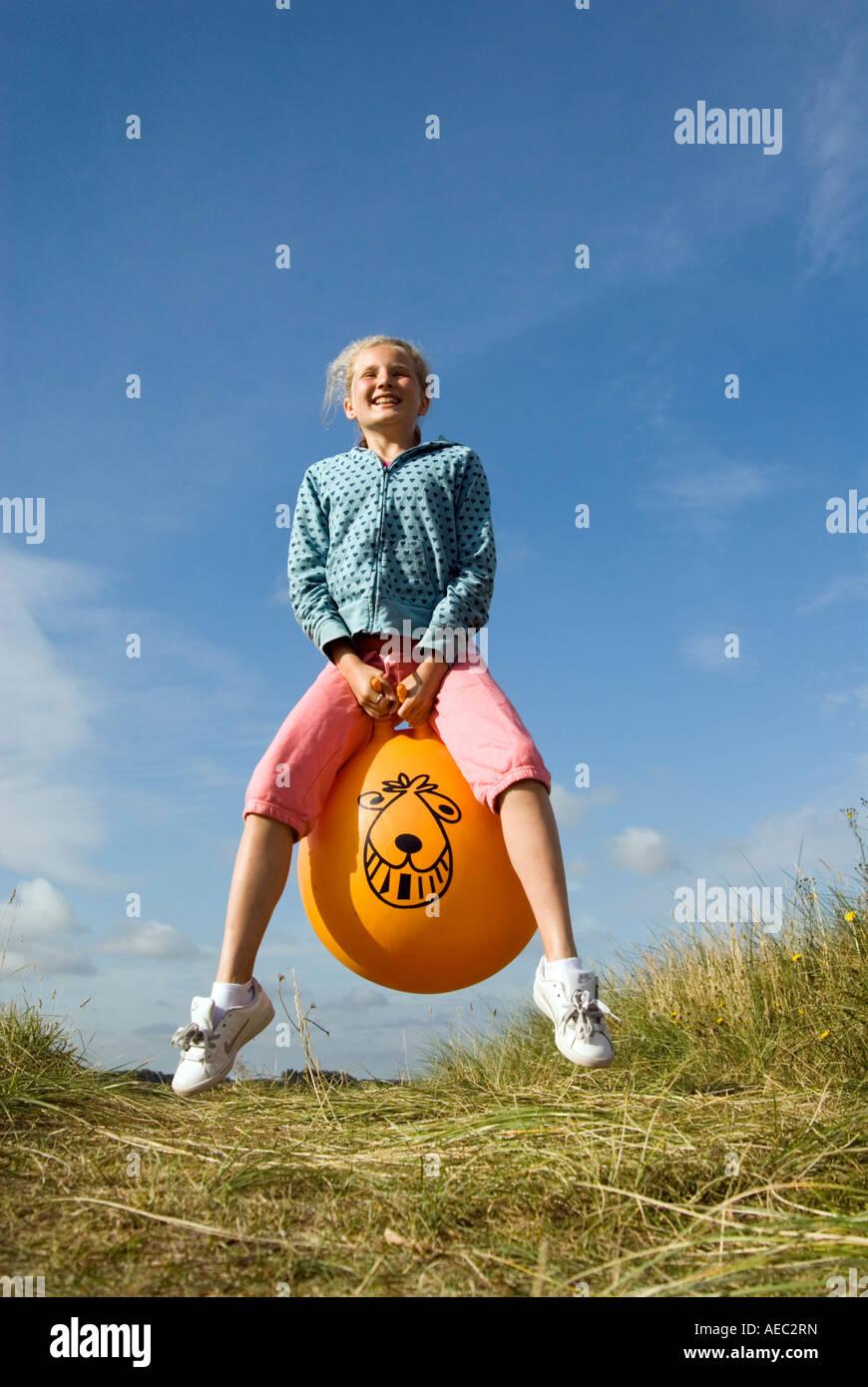 Junges Mädchen hüpfen auf einem Space Hopper, England UK Stockbild