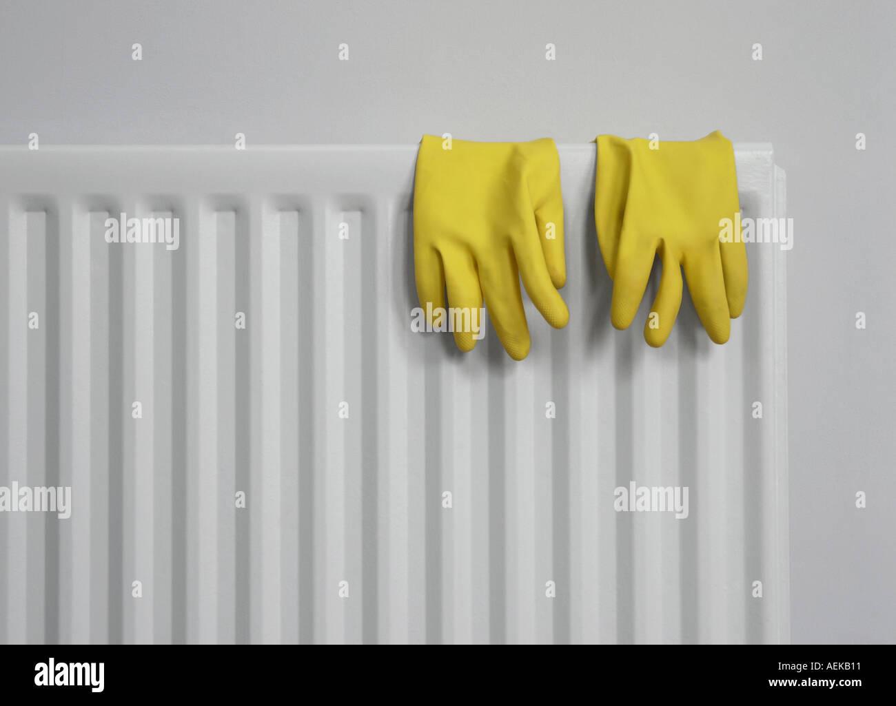 Gelbe Gummihandschuhe auf grauen Heizkörper Stockbild