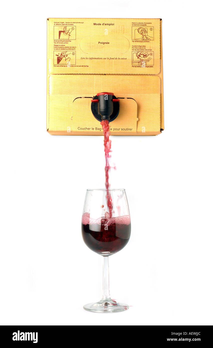 Rotwein aus einem Feld in ein Weinglas gegossen Stockfoto