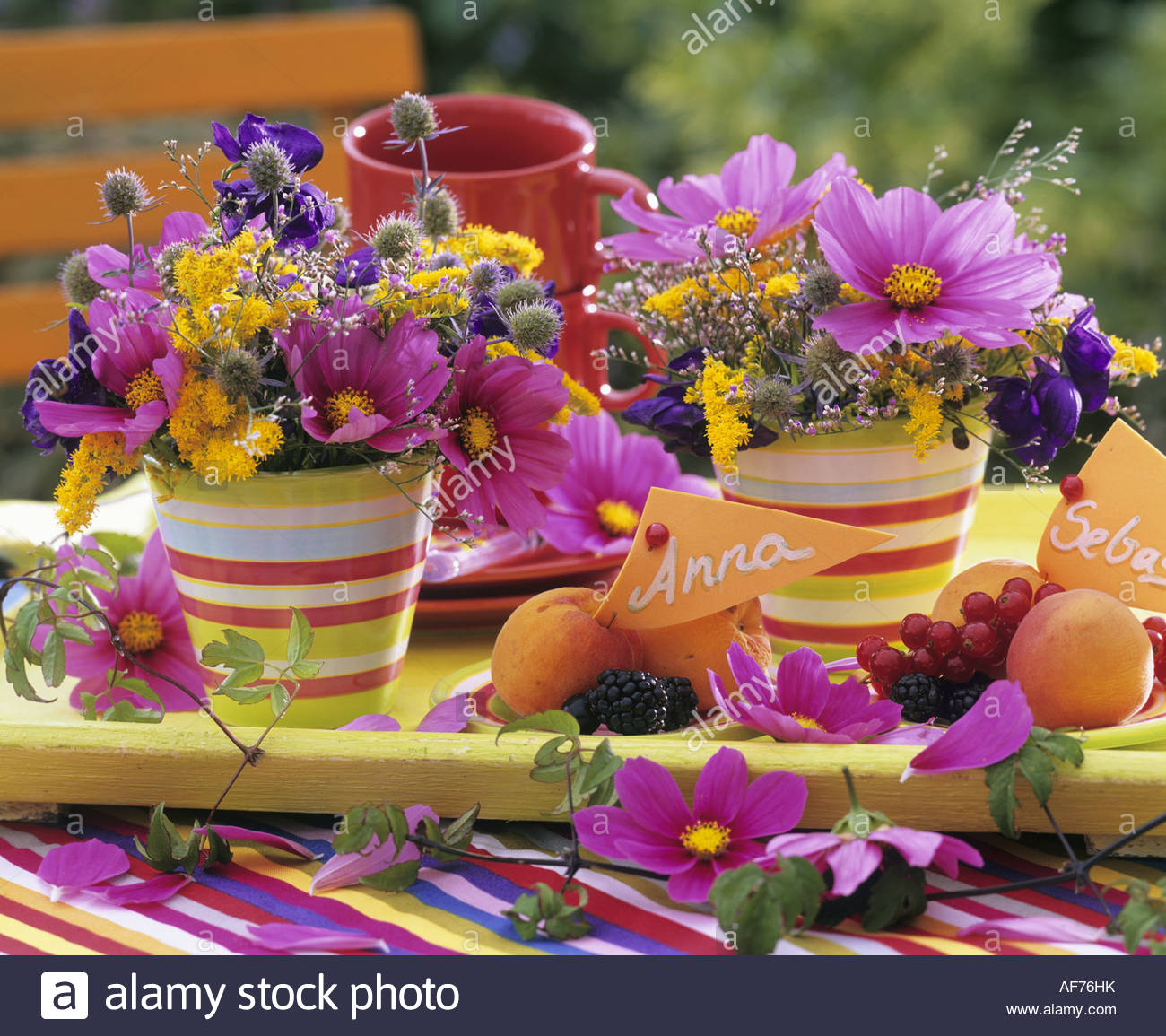 Farbenfrohe Blumenarrangements & Platten von Früchten mit Tischkarten Stockbild