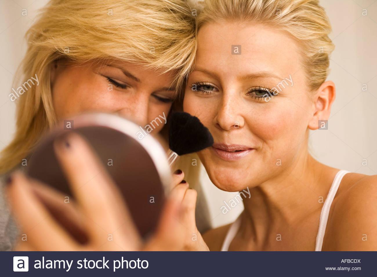 Nahaufnahme einer jungen Frau, die Anwendung von erröten Stockbild