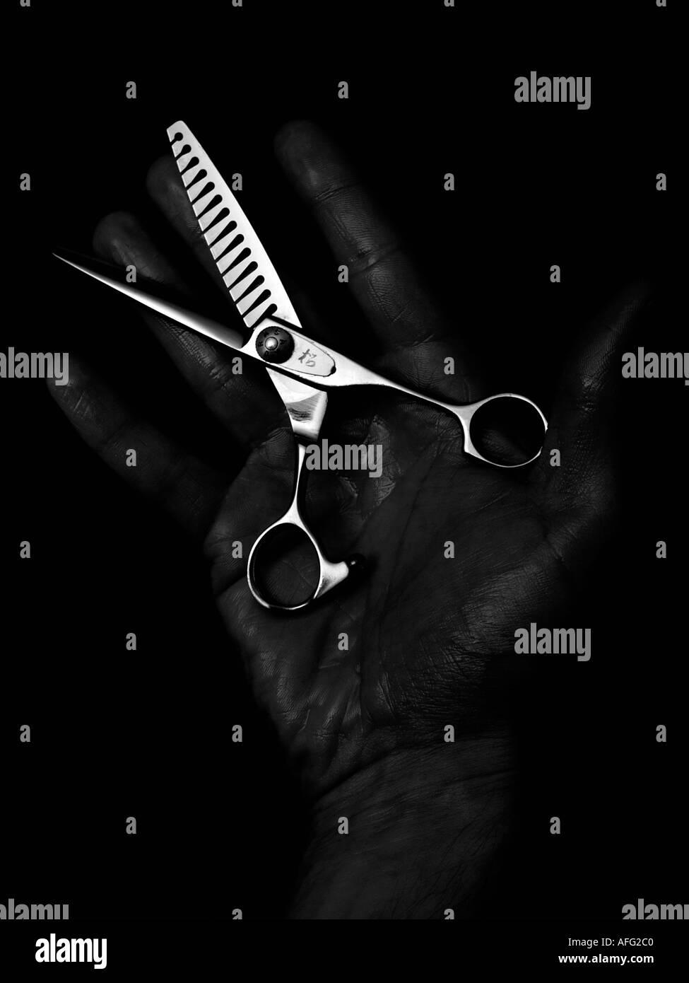 Einfarbige dunkle zurückhaltend Schuss von einem mans Hand mit ganz besonderen Friseur Schere Scheren Stockfoto