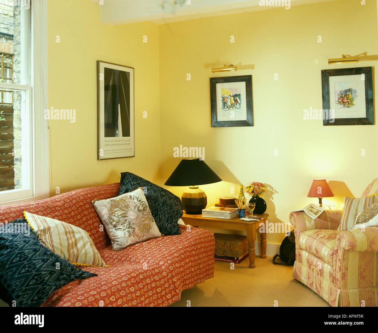 https://c8.alamy.com/compde/afnf5r/pastell-gelb-wohnzimmer-mit-lampe-auf-dem-tisch-in-der-ecke-und-gemusterten-rot-zu-werfen-auf-dem-sofa-afnf5r.jpg