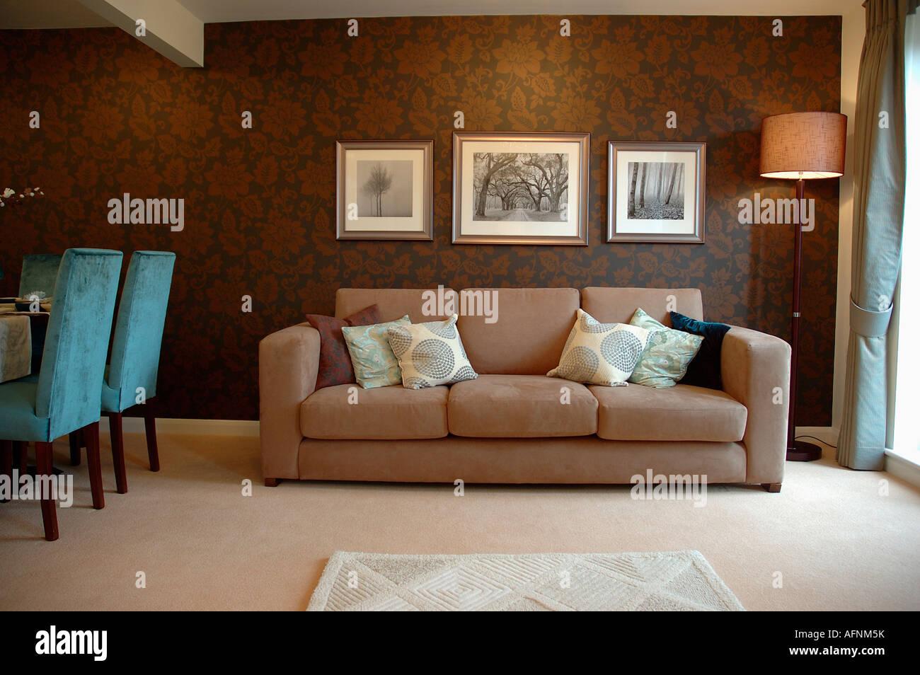 Modernes Apartment Wohnzimmer Mit Braun Gemusterten Tapeten Und Bilder An  Die Wand über Dem Braunen Sofa Mit Kontrastierenden Kissen Creme
