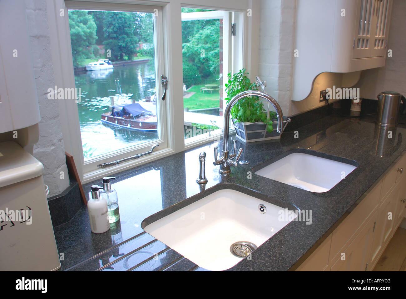 Zwei weiße Waschbecken in Granit Arbeitsplatten vor Küchenfenster ...