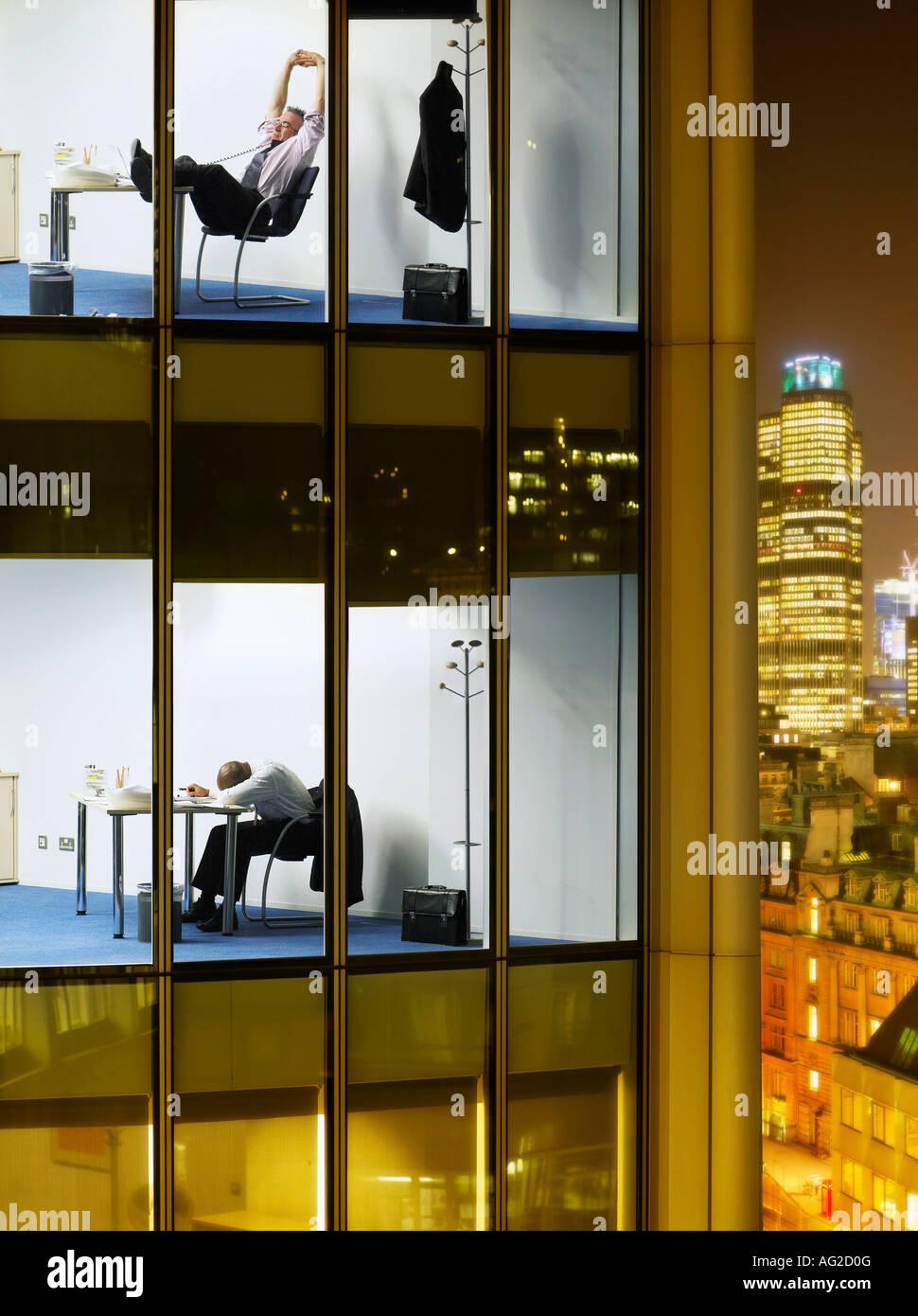 Müde Geschäftsleute in Büros, Blick vom Gebäude außen Stockbild