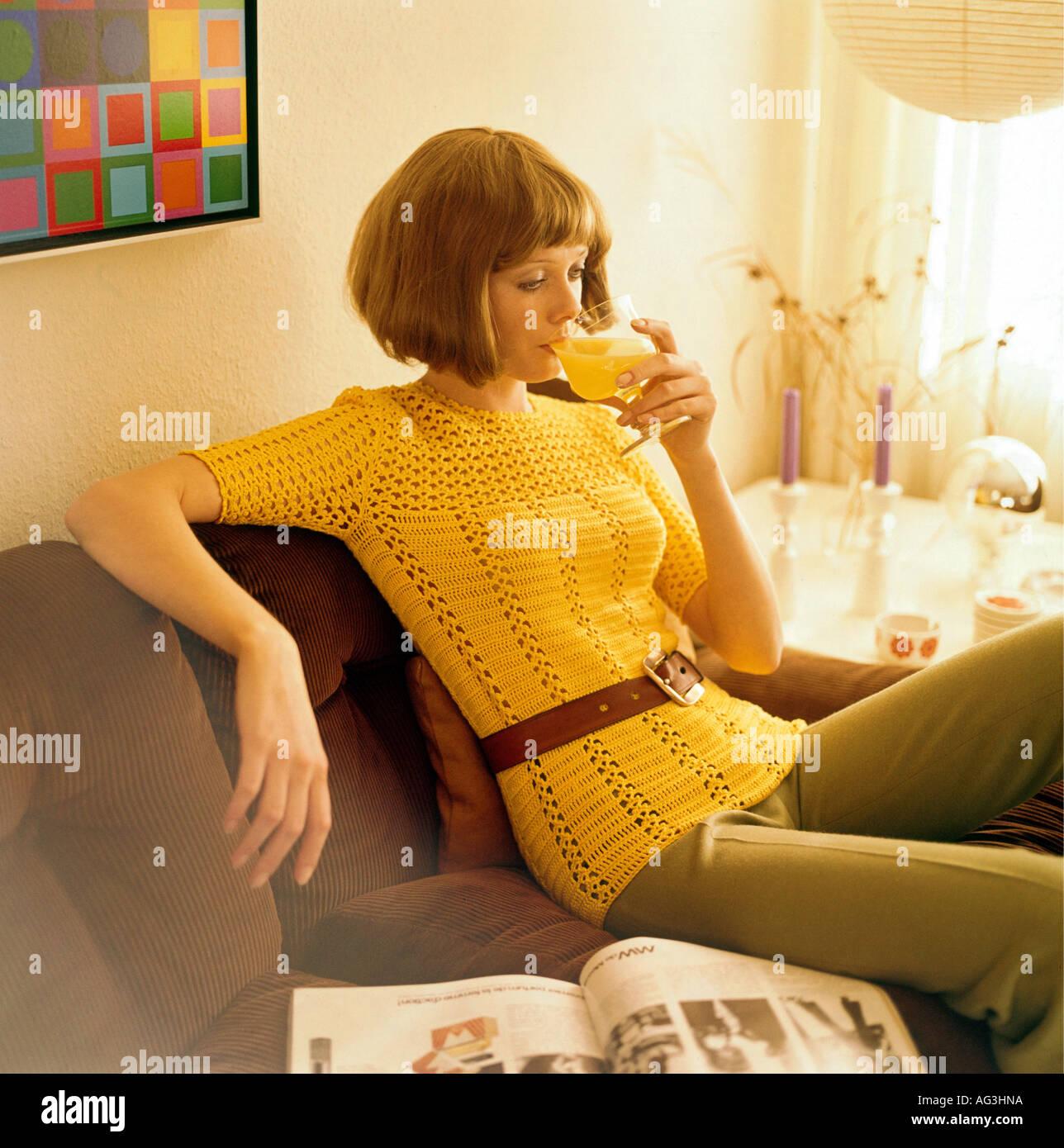 Menschen, Frauen, 1960er Jahre, Frau sitzt auf einem Sofa und trinken Orangensaft, halbe Länge, Mode, 60s, historischen, geschichtlichen, Pullover, andere als aus Gewirken, Häkeln, Pageboy Stil, 20, weiblich, Additional-Rights-Spiel-NA Stockbild