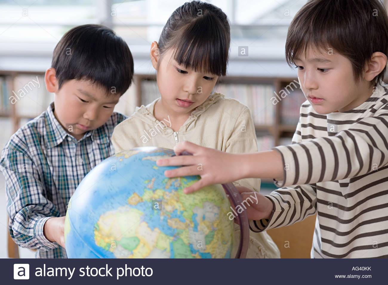 Kinder betrachten einen Globus Stockbild