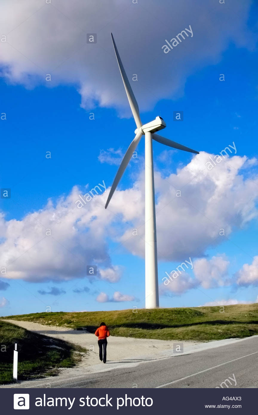 Eine Frau auf dem Weg zu einer Windkraftanlage Stockbild