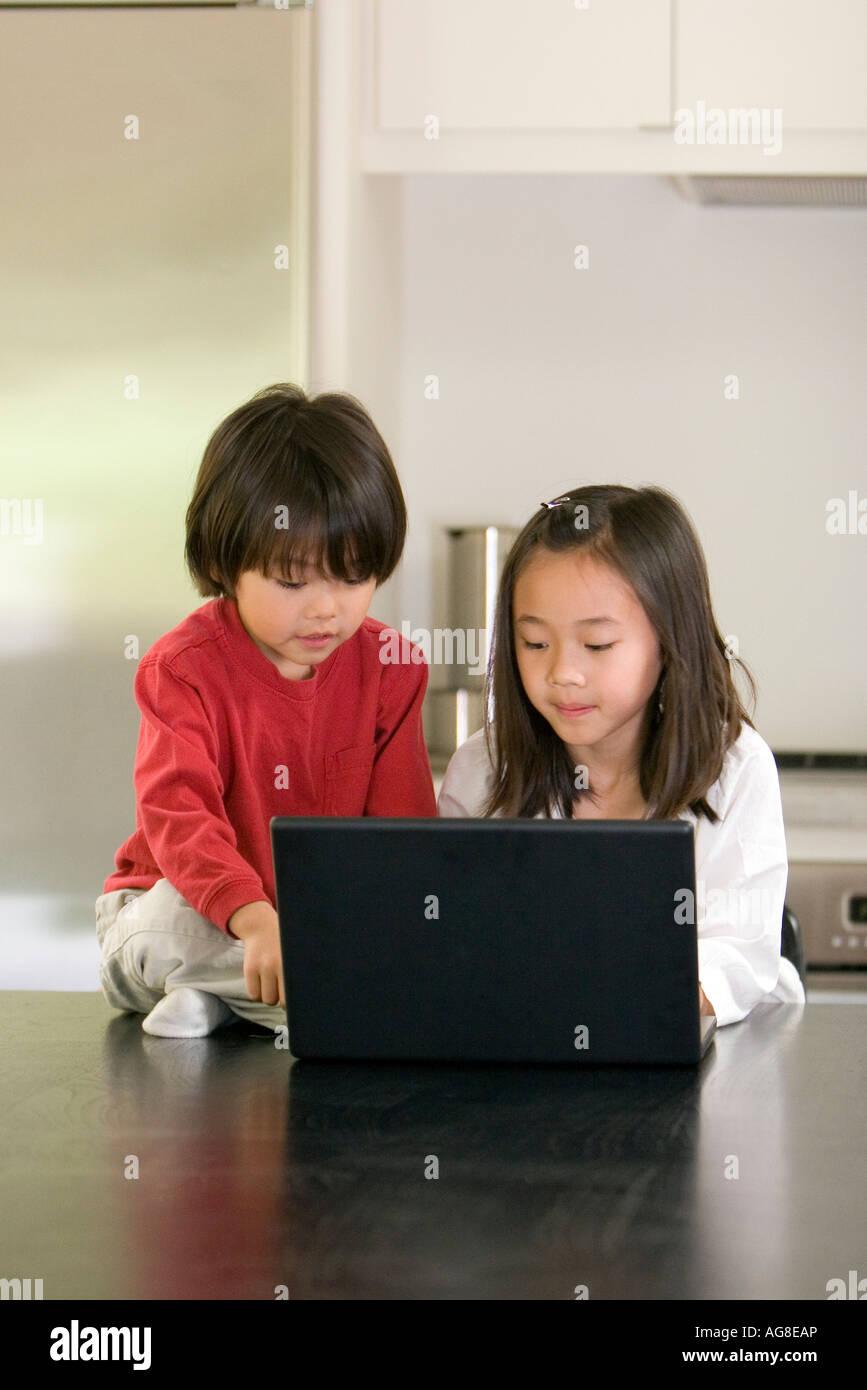 Junge Mädchen und Jungen auf Laptop Stockfoto