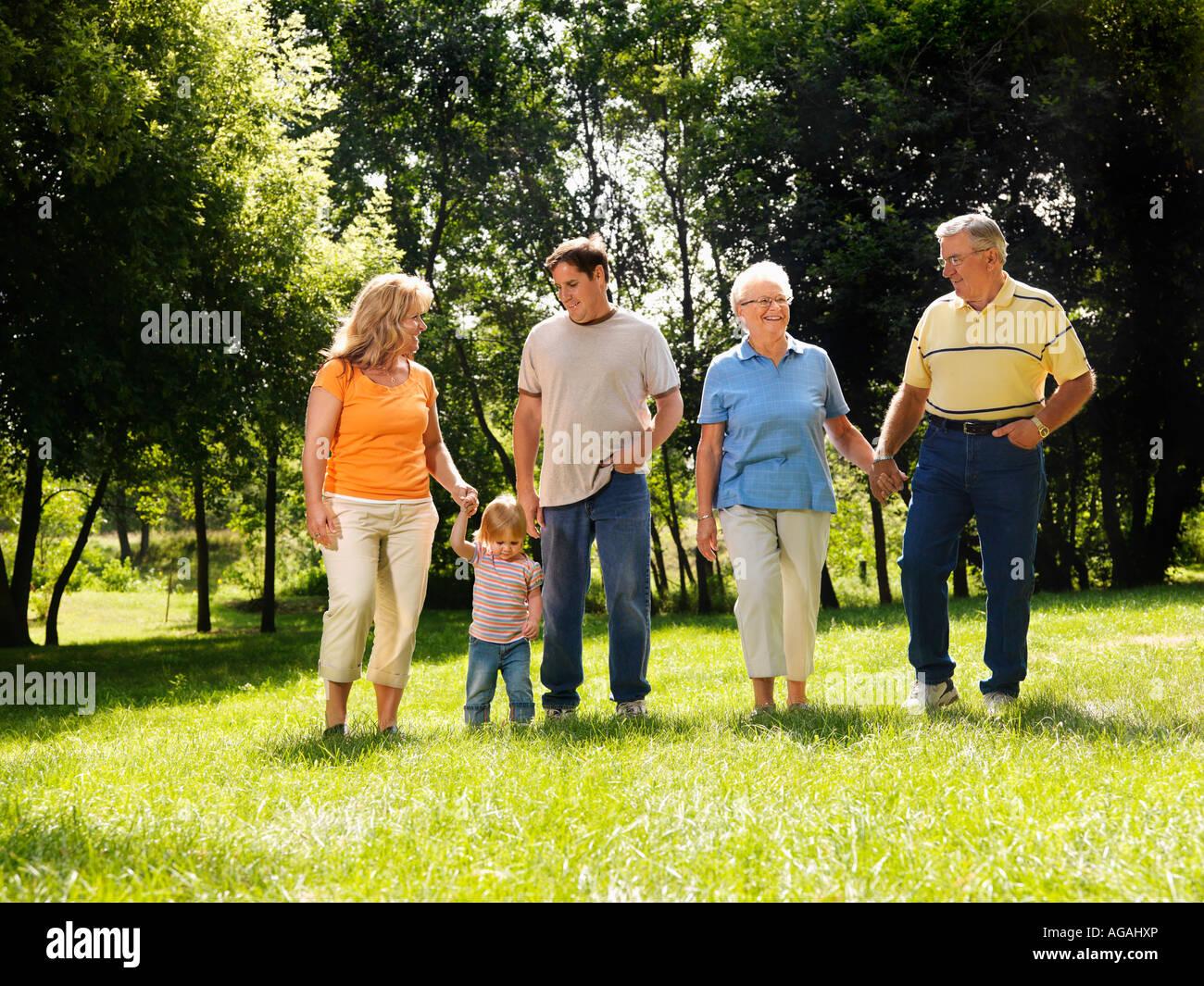 Drei Generationen kaukasische Familie Hand in Hand zu Fuß über den Rasen im Park lächelnd Stockbild