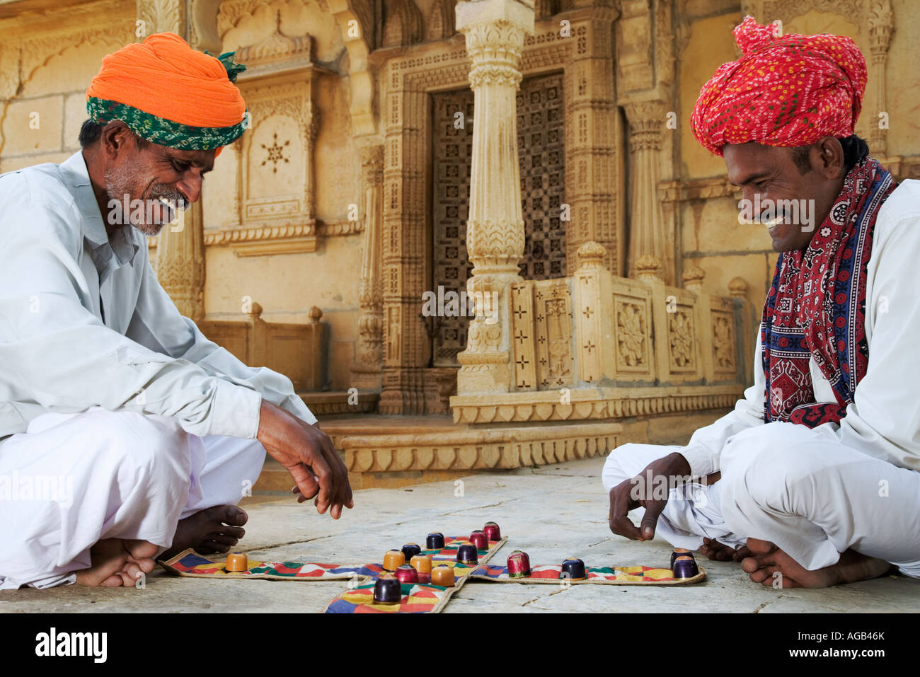 Zwei Männer spielen traditionelle Hindu Spiel Chopar vor dem Shiva-Tempel am See GadisarStockfoto