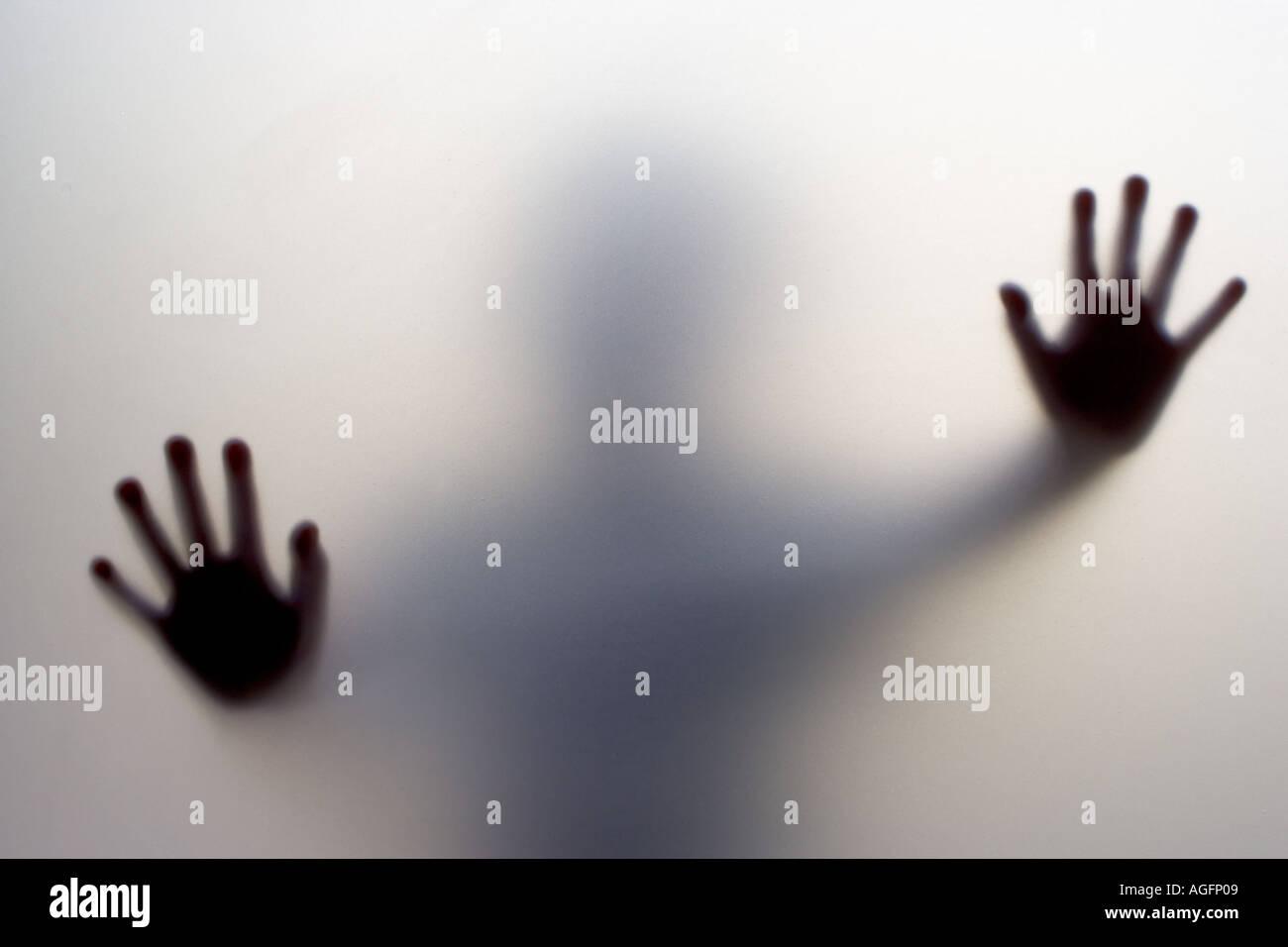 Die Hände eines Kindes an das Milchglas einer Tür gedrückt Stockbild