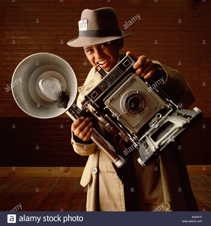 Junge mit Kamera tragen alte altmodische Regenmantel und Hut Stockbild