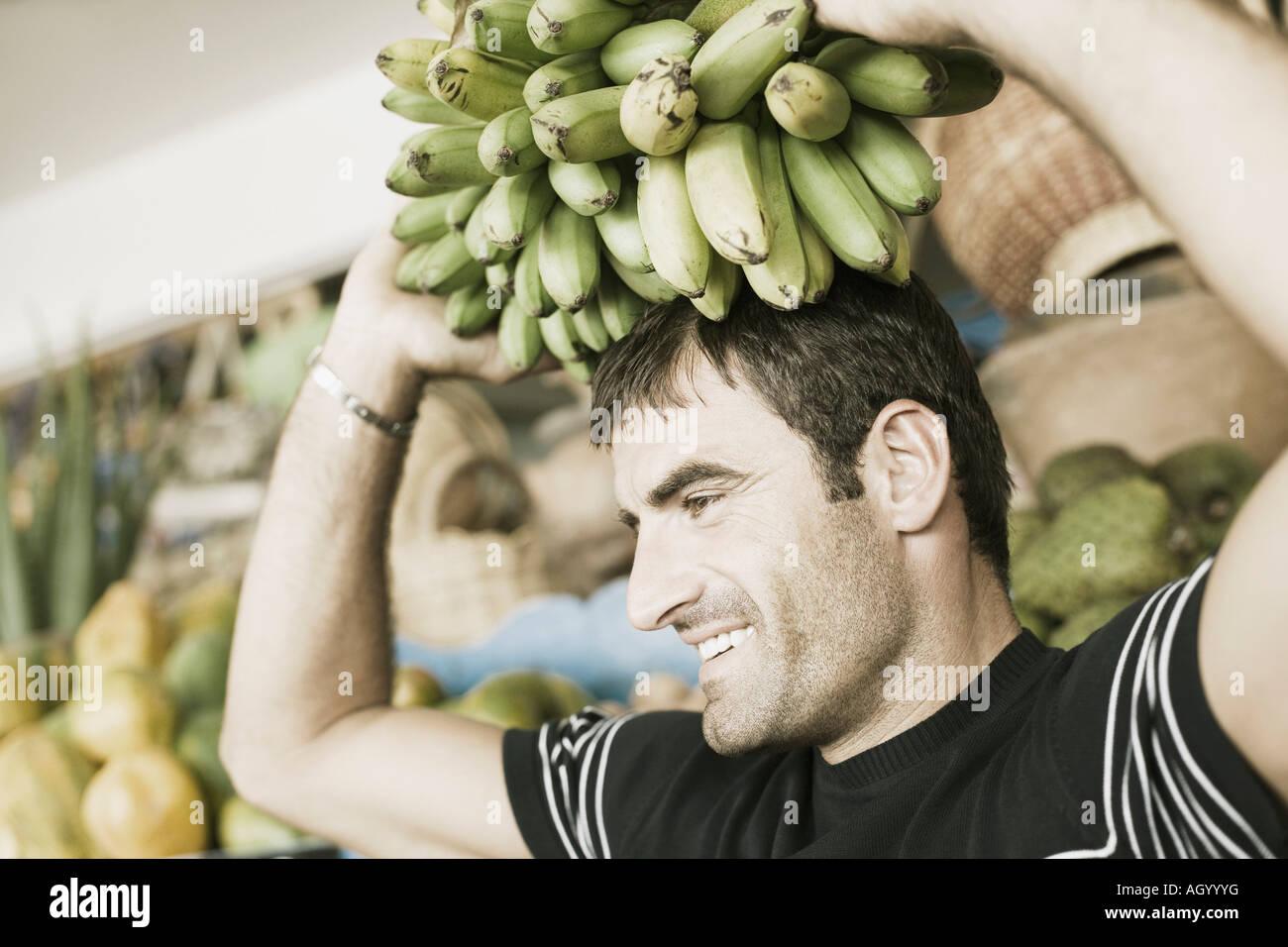 Nahaufnahme eines Mitte erwachsenen Mannes trägt ein Bündel Bananen auf dem Kopf Stockbild