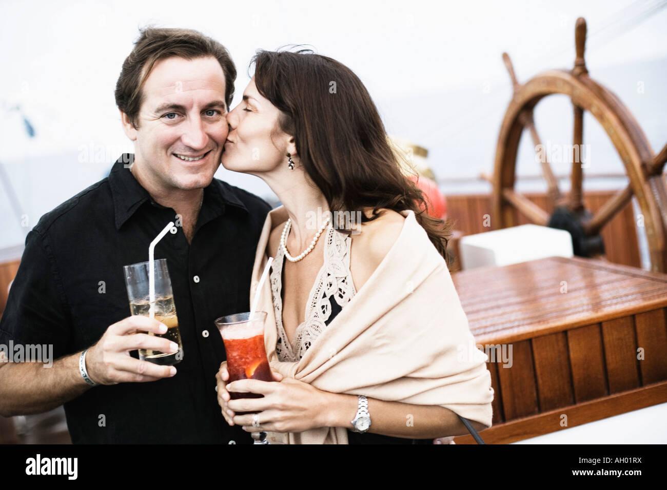 Mitte Erwachsene Frau küssen einen Mitte erwachsenen Mann auf einem Segelschiff Stockbild