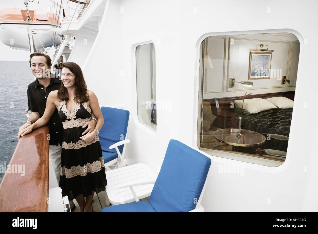 Mitte erwachsenes paar stehen an der Reling eines Segelschiffes und lächelnd Stockbild