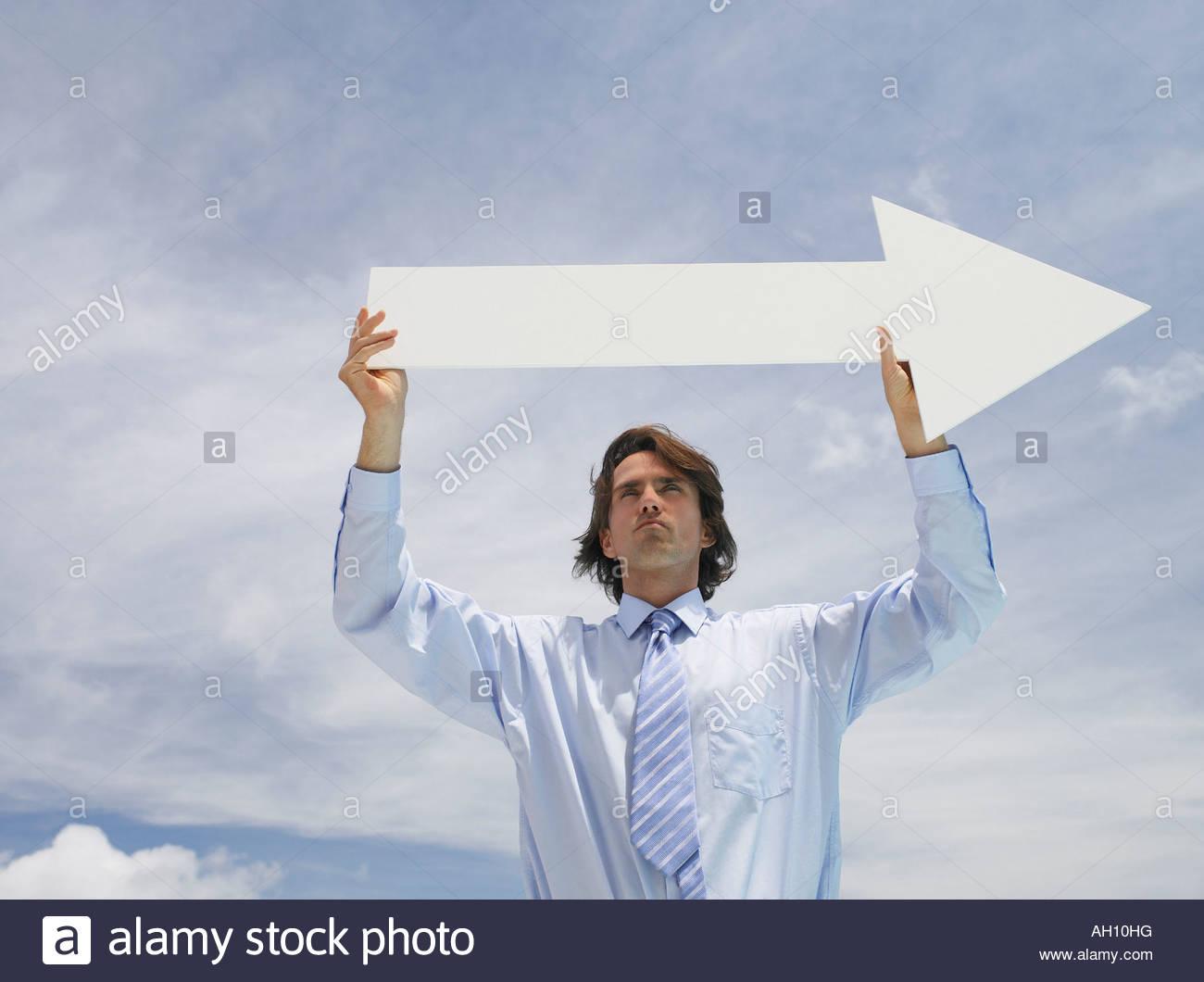 Geschäftsmann, draußen halten leere Pfeil mit Himmel im Hintergrund Stockbild