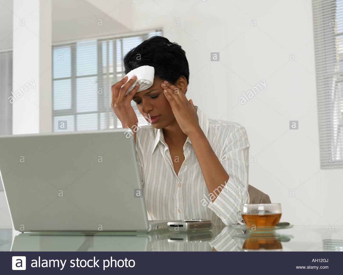 Eine Geschäftsfrau auf einem Laptop mit Kopfschmerzen Stockbild