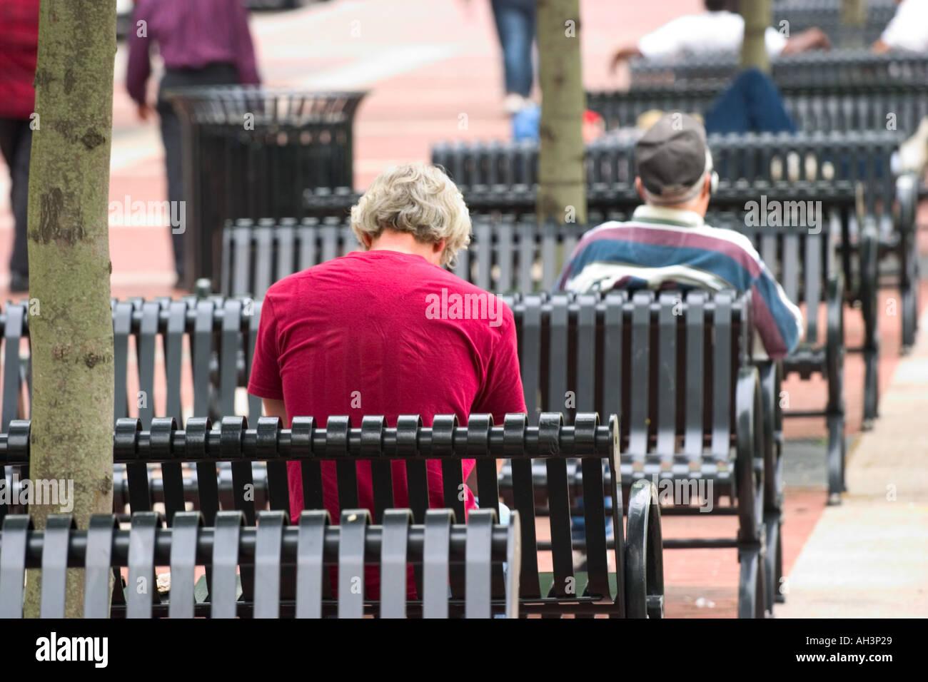 Männer sitzen draußen auf Metall Stadt Bänke Stockfoto, Bild ...