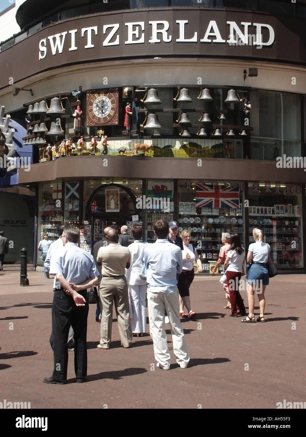 Street Scene Schweizer Tourist Information Office Shop & Leute beobachten, die mitlaufende Uhr Anzeige der Kühe Milchfrauen & läuten Glocken Leicester Square London, Großbritannien Stockfoto
