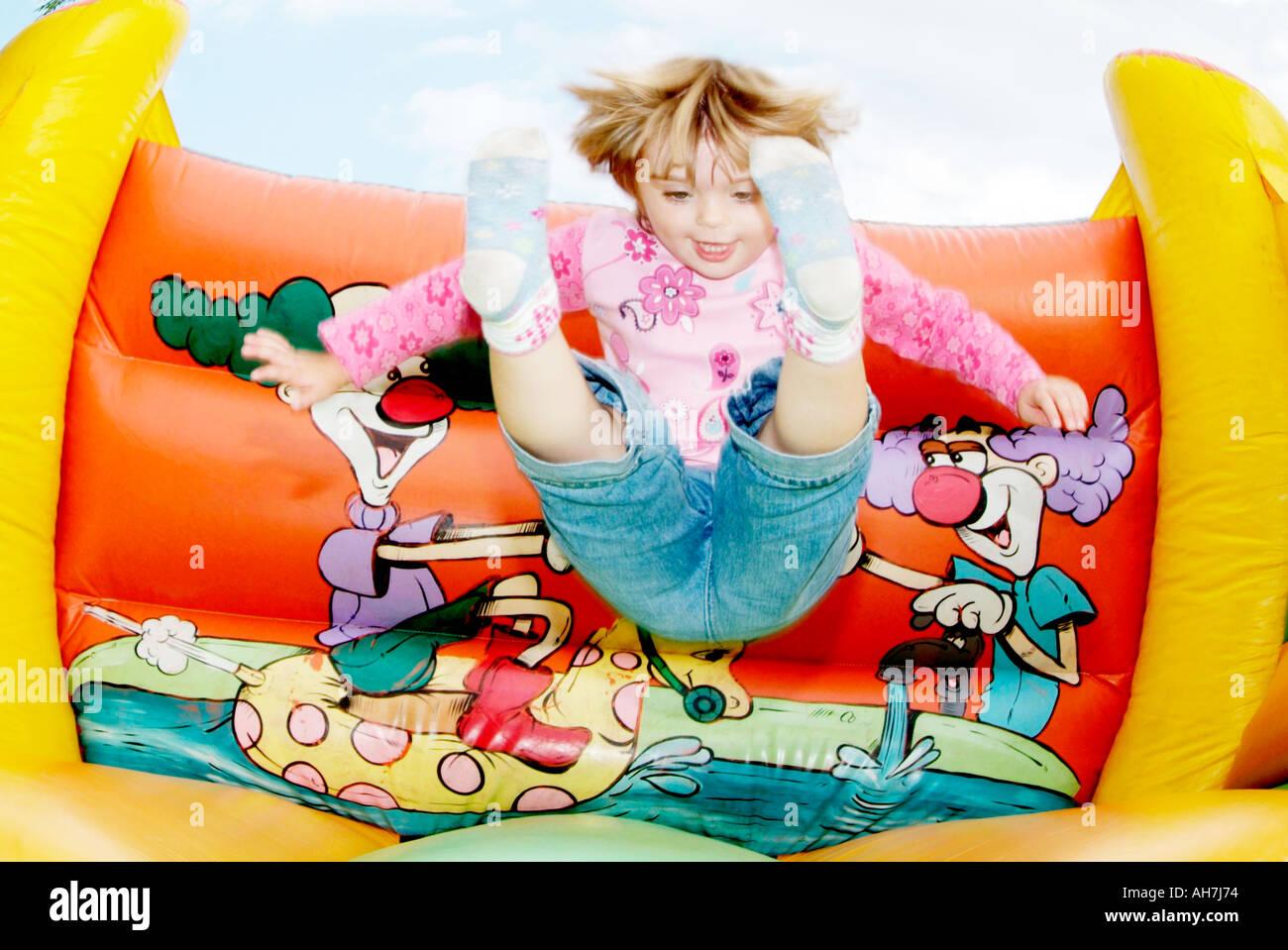 glückliches Kind spielt auf einer Hüpfburg Spielspaß Spaß Spaß Bounce springen Frühling Energie hyperaktiv Lächeln Fliege fliegen Screa Stockbild