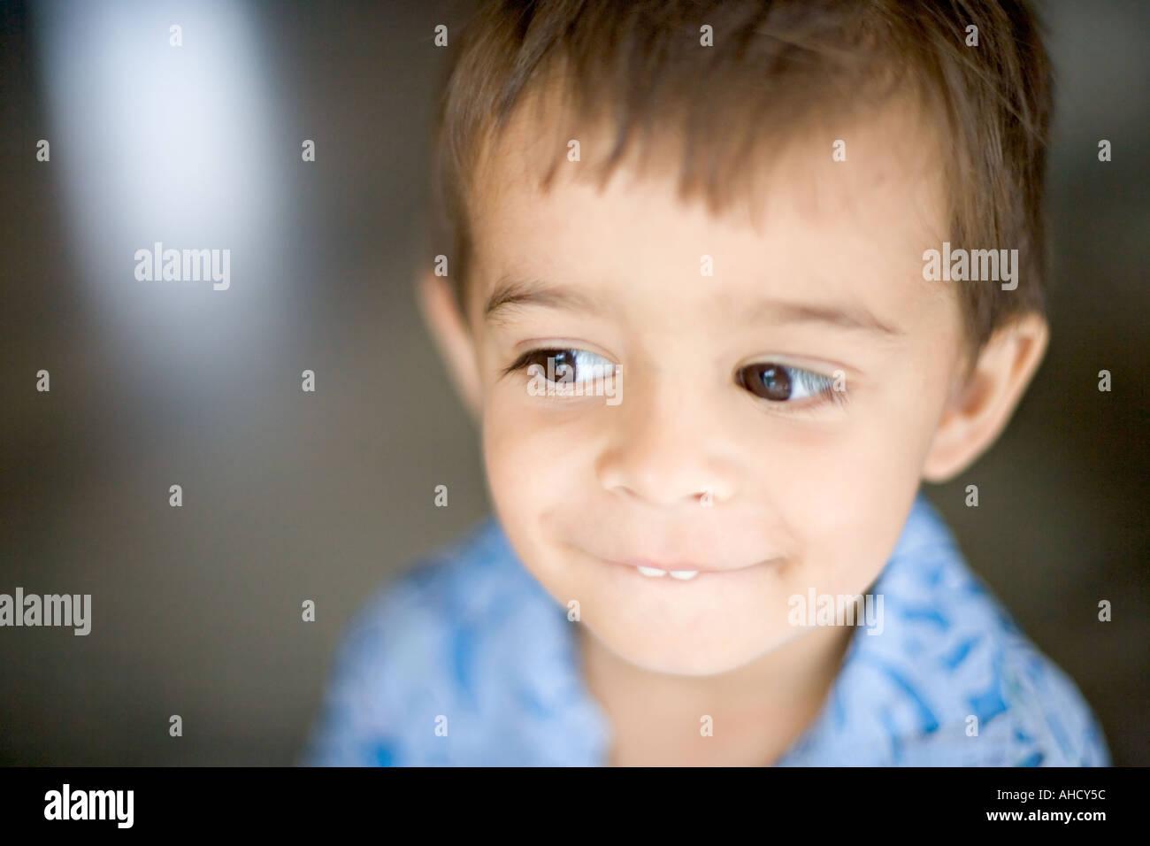 Kamera schaut auf einen niedlichen kleinen Jungen mit braunen Haaren und einem frechen Lächeln Stockbild