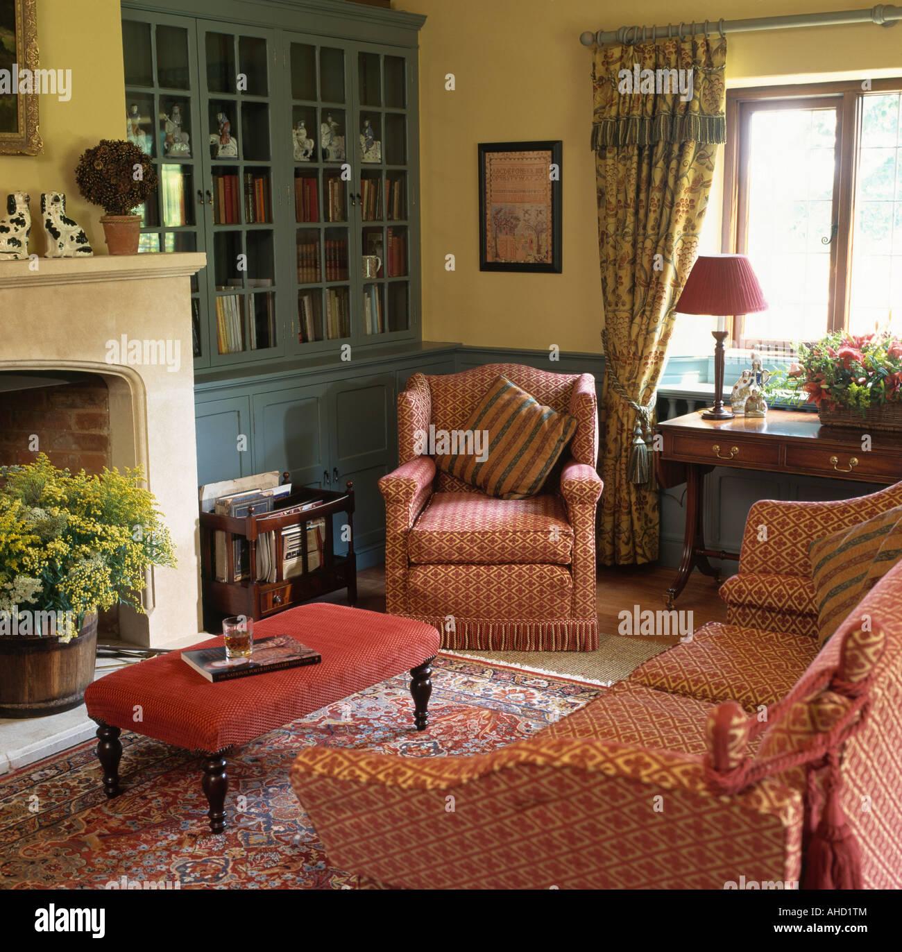 Gemusterte Rotes Sofa Und Sessel Im Wohnzimmer Mit Blass Gelben Wänden Und Grau  Blau Alkoven Schrank