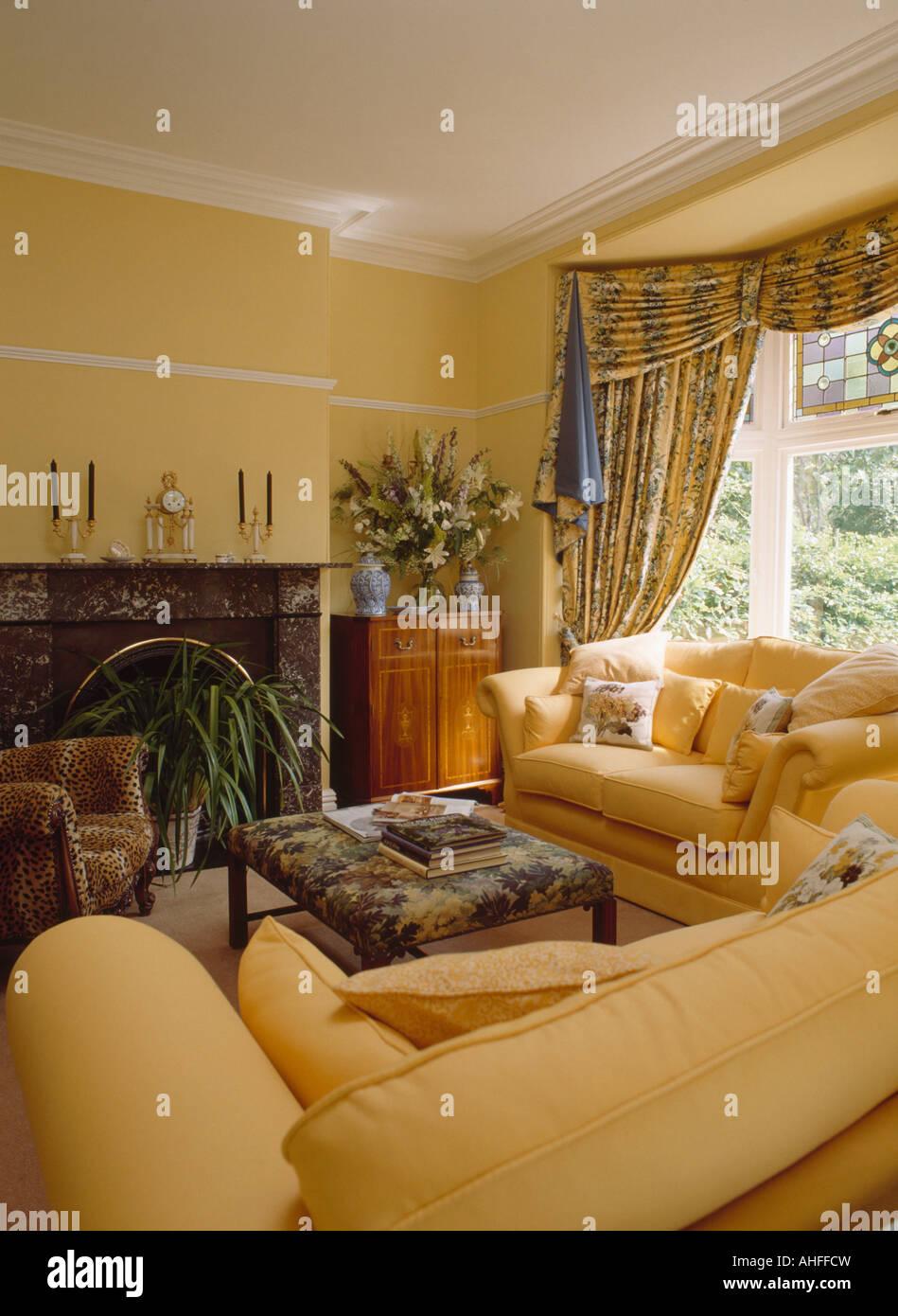 blaue und gelbe swagged vorh nge in pastell gelb wohnzimmer mit blass gelben sofas stockfoto. Black Bedroom Furniture Sets. Home Design Ideas