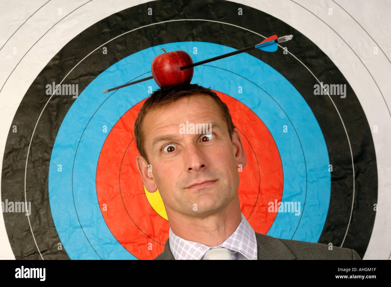 Geschäftsmann vor ein Ziel mit einem Apfel und Pfeil auf dem Kopf Stockbild