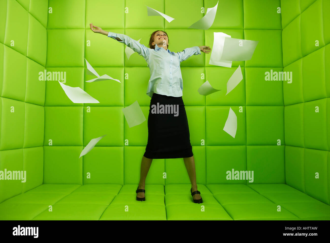 Frau warf Papiere rund um grüne Gummizelle Stockbild