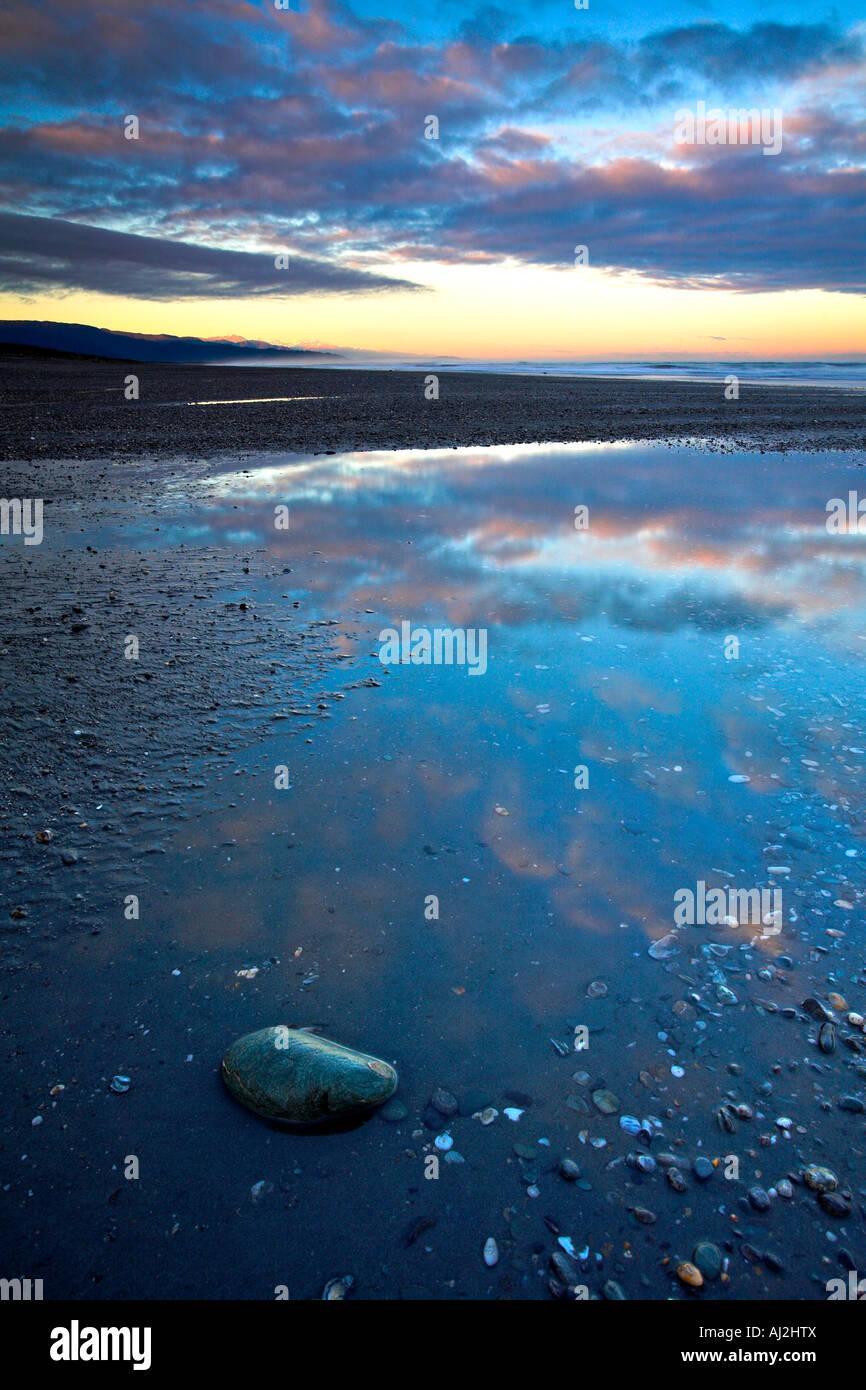 Einem entfernten Westküste Strand im Morgengrauen den Sonnenaufgang Glitzern auf die Bergkette der südlichen Stockbild