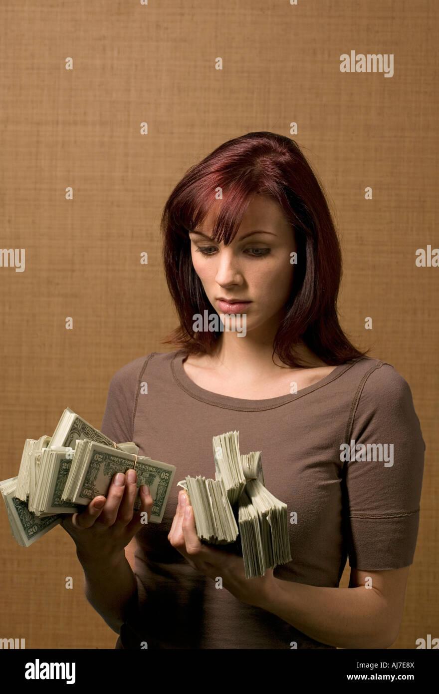 roten Haaren 25 bis 30 Jahre alte Frau Stapel von Geld in ihren Händen hält Stockbild