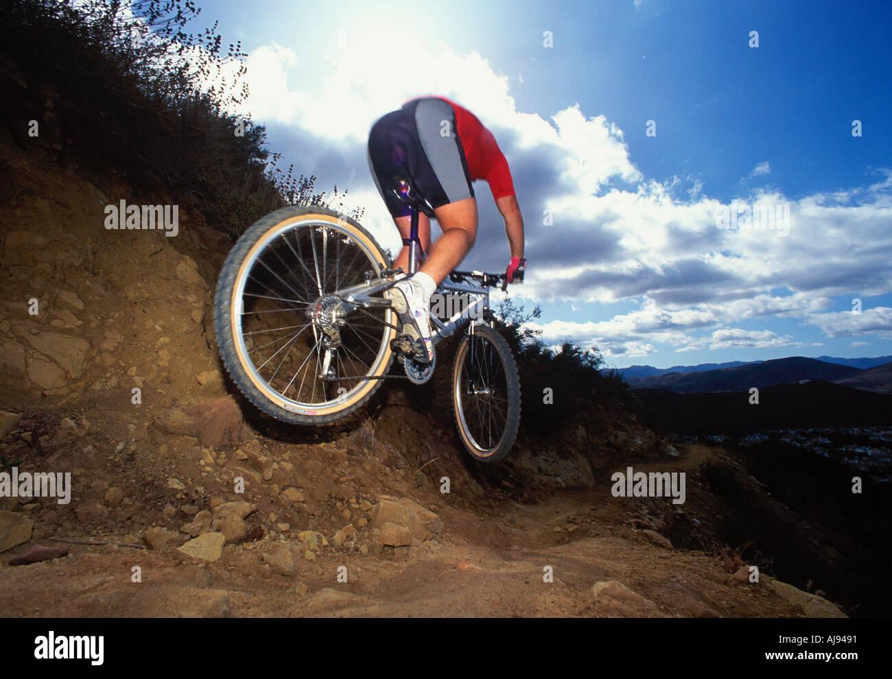 Ein Mountainbiker springen einen Hügel hinunter auf ein Singletrack trail Stockfoto