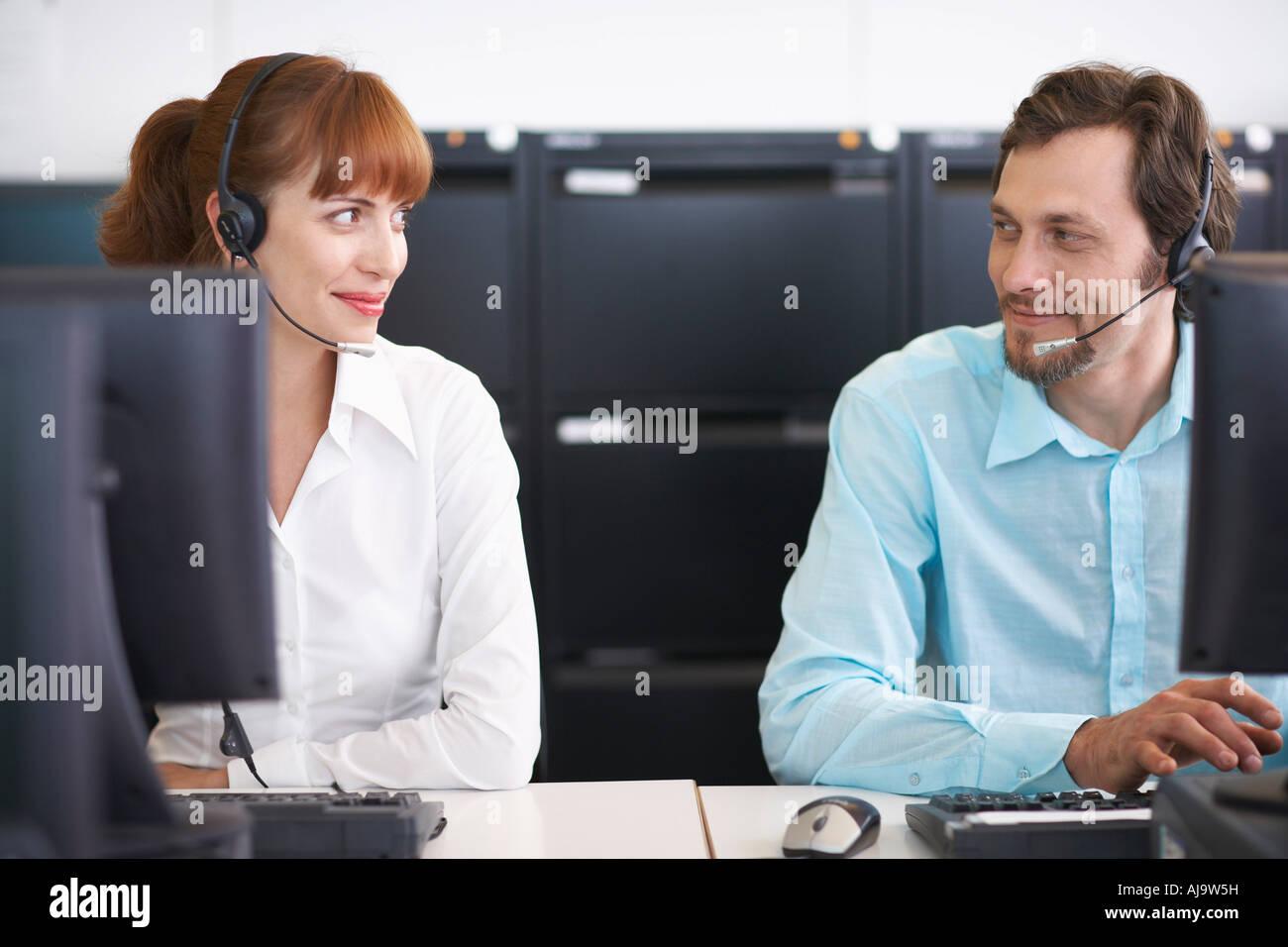 Geschäftsleute, die auf Computern mit Headsets Stockfoto