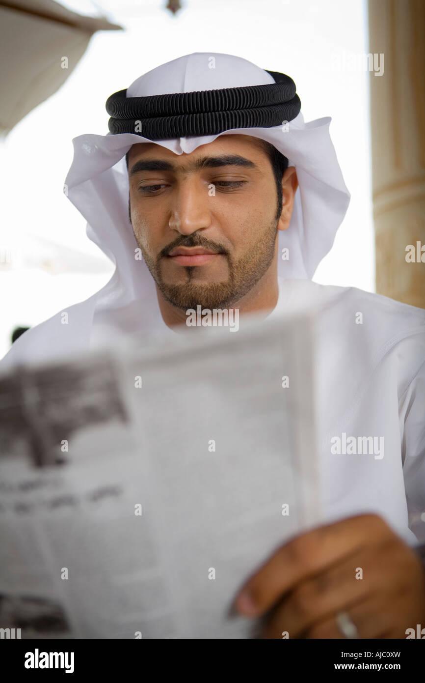 Arab Business Mann lesen Zeitung auf Terrasse Stockbild