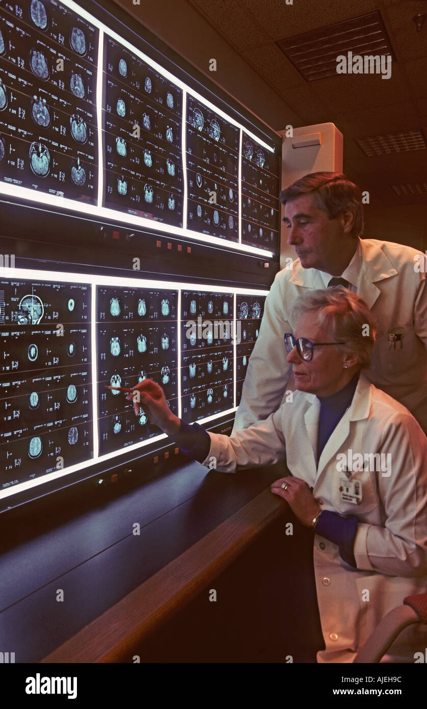 männliche und weibliche Ärzte Blick auf MRT-Aufnahmen Stockbild