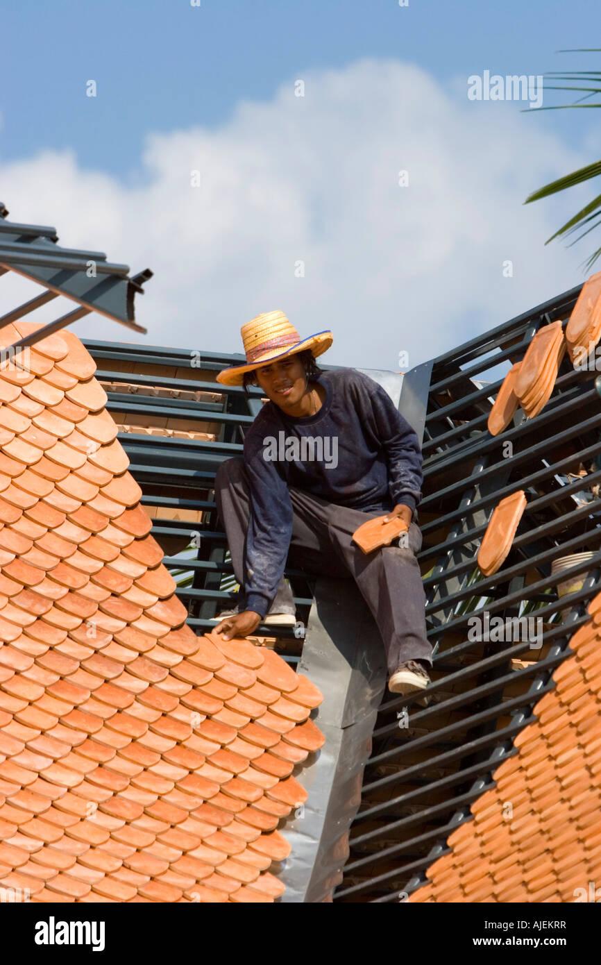 Dachdecker positioniert Fliesen auf neue Dachrahmen nach Tsunami ...