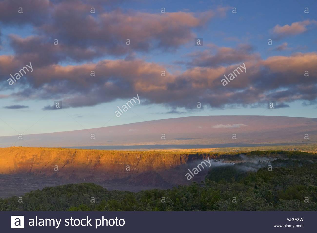 Der Sonnenaufgang Farben am Himmel über dem Kilauea Caldera und Mauna Loa in dieser Ansicht aus Hawaii Volcanoes Stockbild