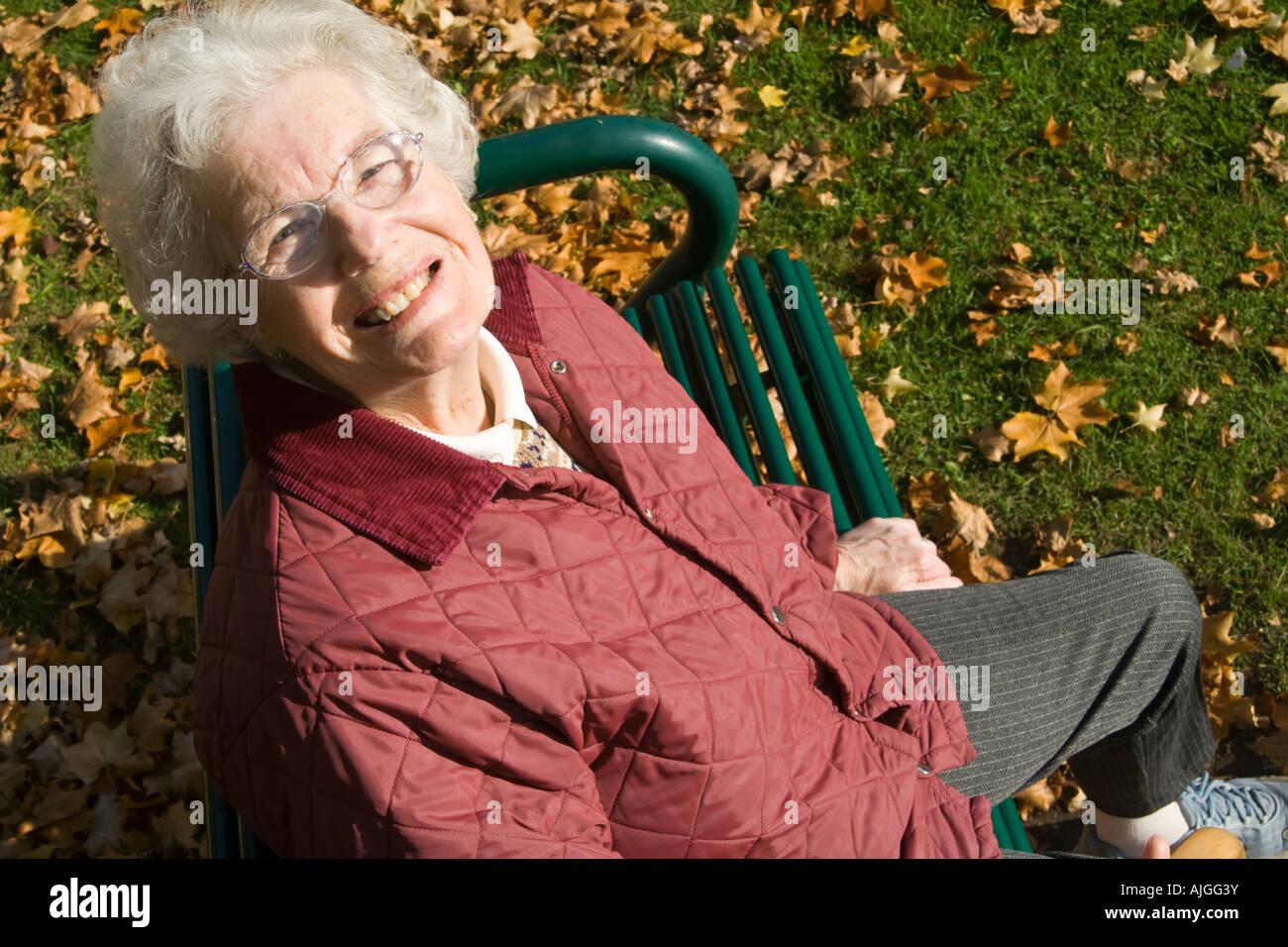 Ältere Dame auf einem Sitz zu sitzen und auf der Suche nach oben Stockbild