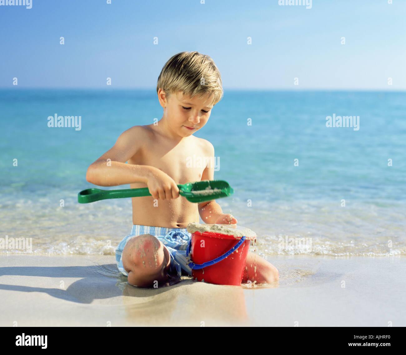 Junge mit nassem Sand spielen Stockbild