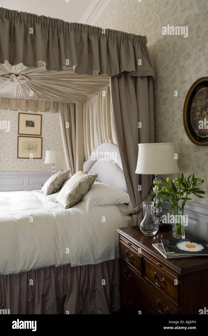 Schlafzimmereinrichtungen Bett mit Profilkranz und Vorhang im Schlafzimmer mit floral gemusterten Tapeten im irischen Stockbild
