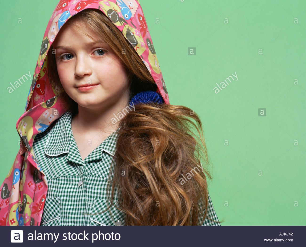 Schulmädchen trägt einen Regenmantel Stockbild