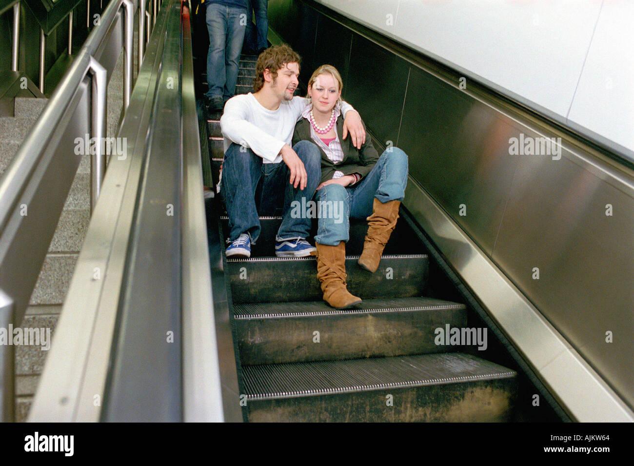 Paar sitzt auf Rolltreppe Stockfoto