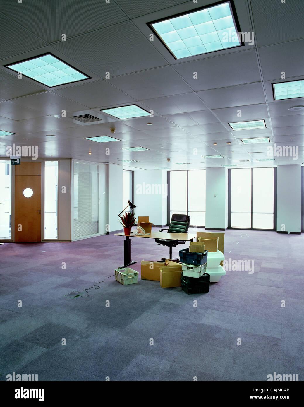 Unordentlichen Schreibtisch in leeres Büro Stockbild