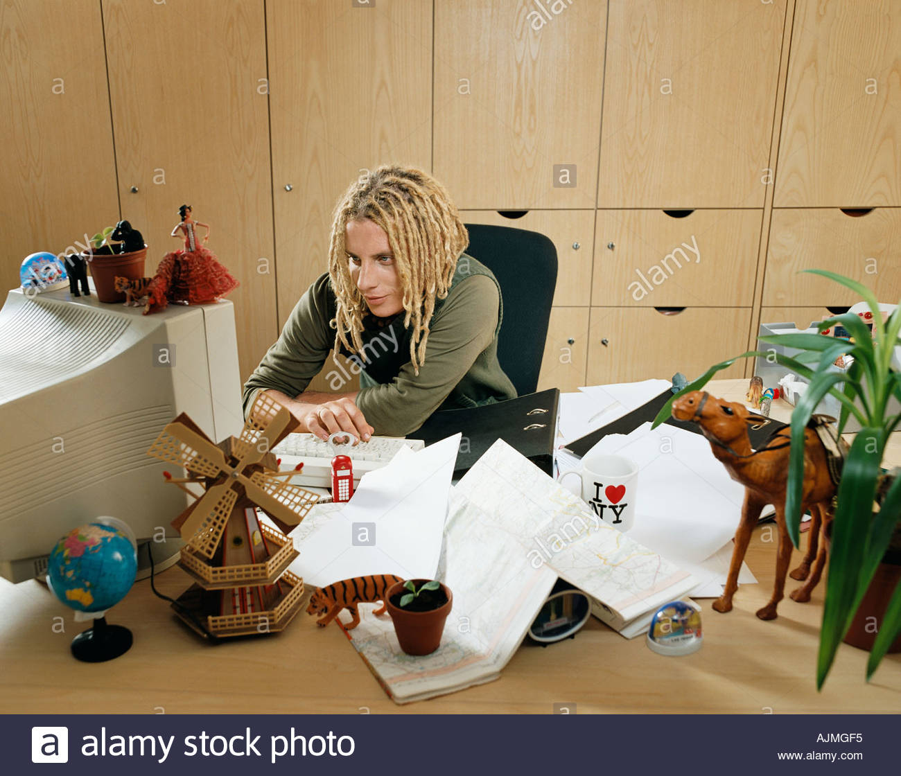Mann mit einem Schreibtisch voller souvenirs Stockbild