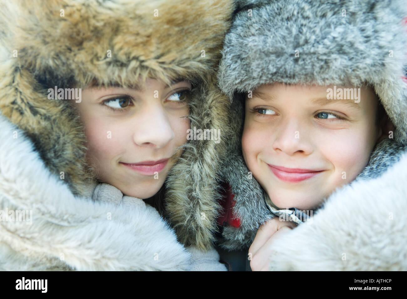 Schwester und Bruder tragen Pelz Mützen, Lächeln, wegschauen, Porträt Stockfoto